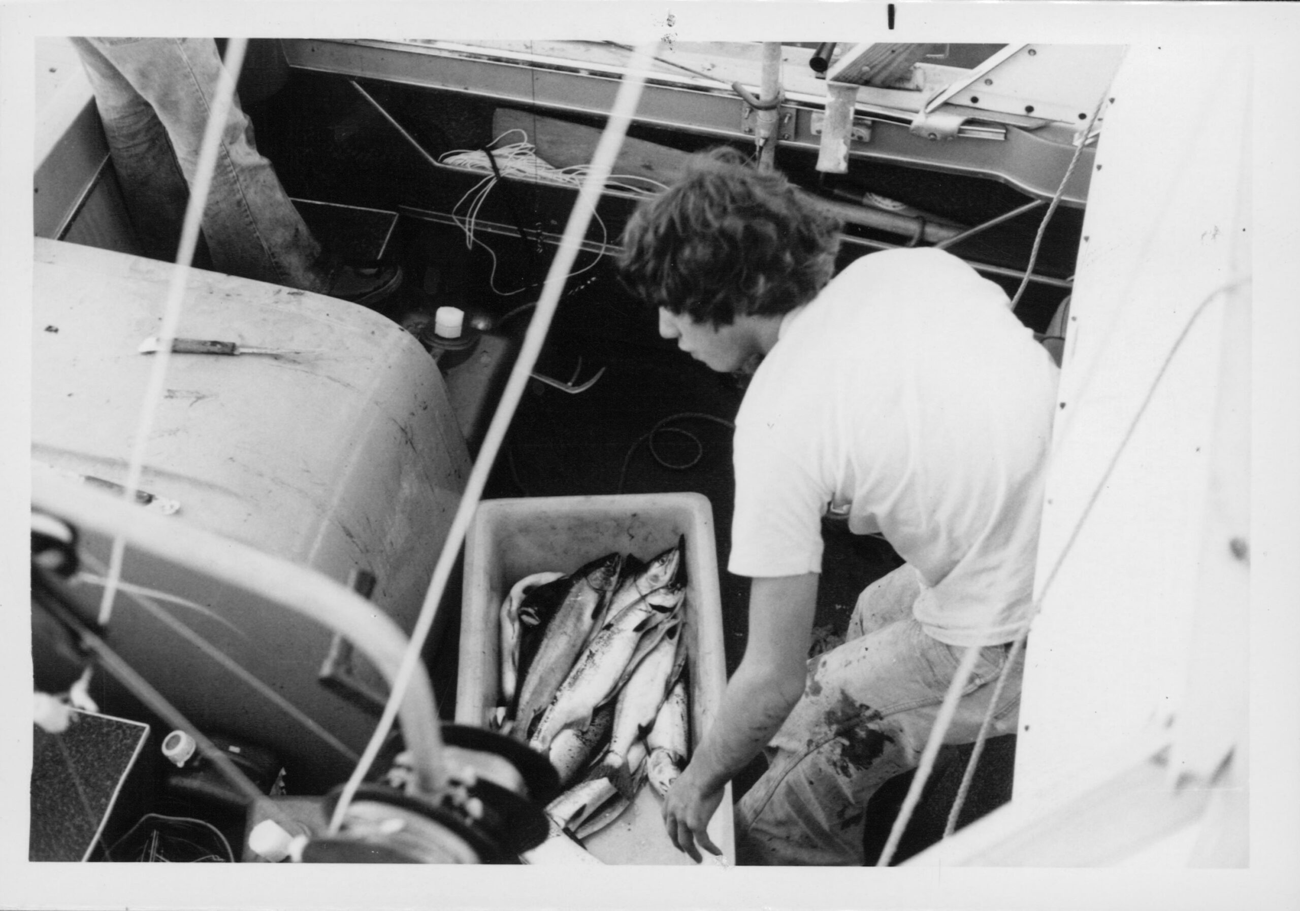 Black and white photo of a young Dr. Al Gross with a large haul of fish on his first boat.